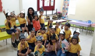 School students showing victory sign with chess piece crown