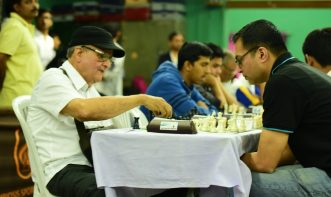 chess match between old and young chess player