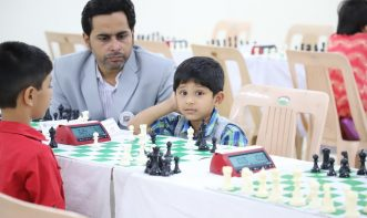 Young players playing chess under coach guidance