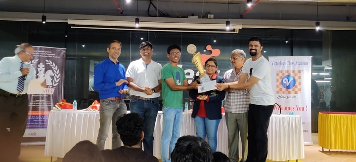 Champion of war of wits tournament Jenil Shah of Citi Bank receiving his champion's trophy and ₹11000 cash